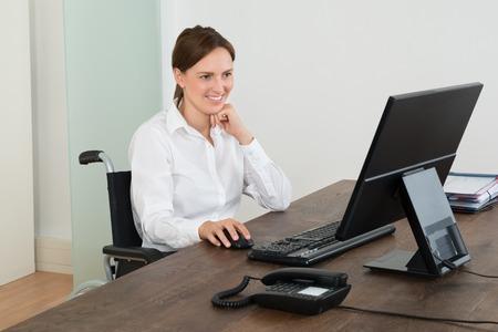 Chica paraplejica contenta mirando ordenador